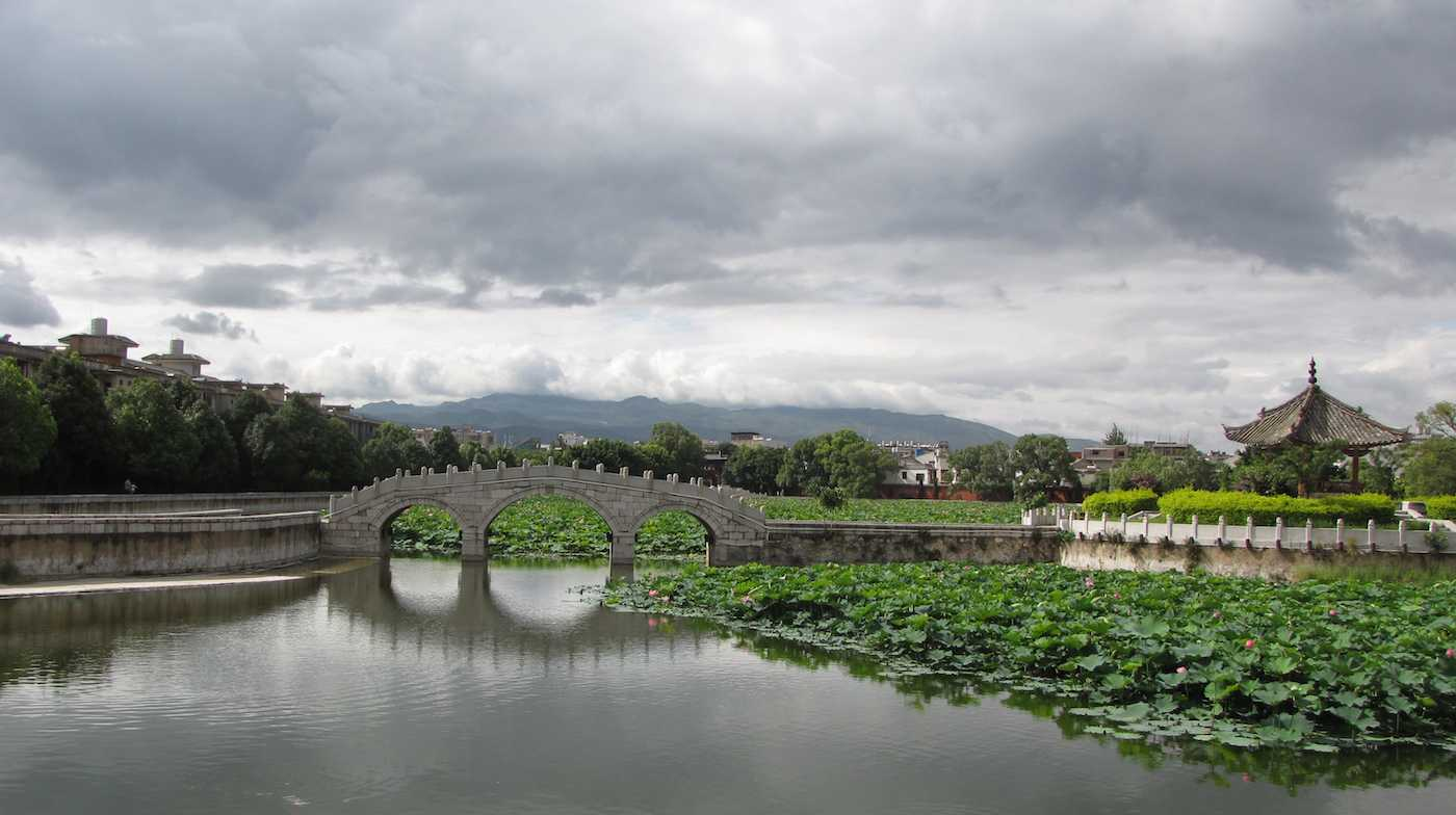 view of bridge over water and mountains in the background